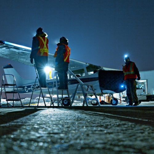 APS team working on ground icing testing at the airport in winter at night
