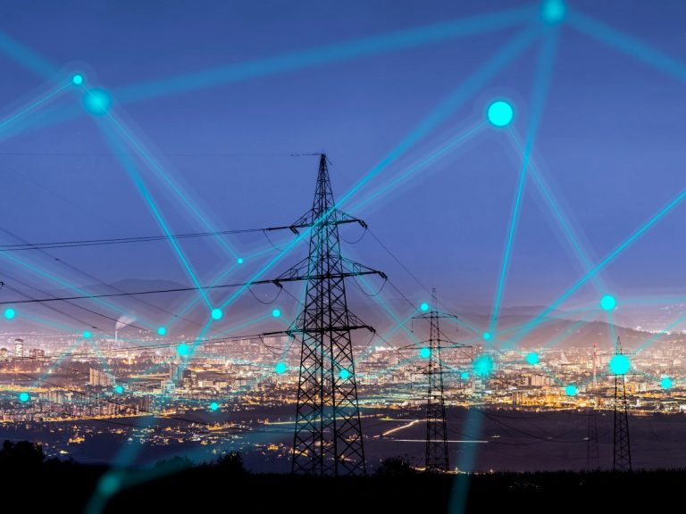 Image of a electric powerplant with a nightfall sky overlayed with digital connectors representing cybersecurity for critical infrastructures