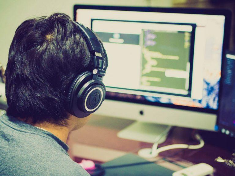 Codeur avec casque devant un écran d'ordinateur travaillant avec CDP4