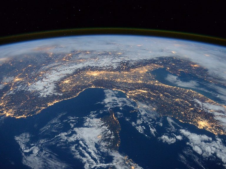 Night view of Earth from space specifically featuring Italy with city lights and the universe behind Earth reflecting RHEA Group's capabilities in space engineering